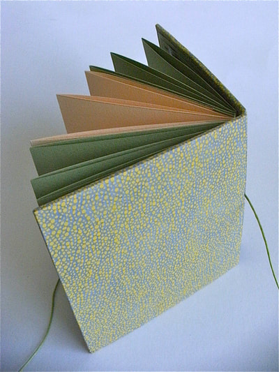 Handmade pocketbook made by Annie Kerr, with bright green covers and moss green and maize coloured plain pages inside.