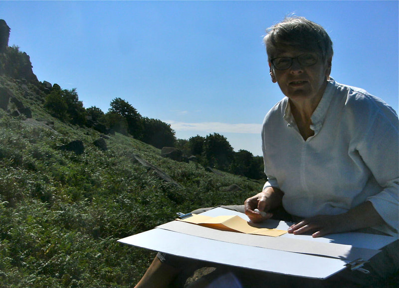Picture of Annie Sketching outdoors on location near rocks at Stanage in the Peak District National Park.