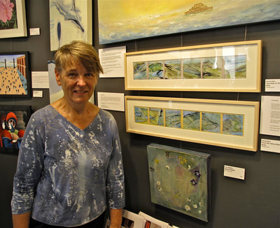 Annie Standing beside some of her framed artwork in art show at Laughing Dog Gallery, Brighton Marina