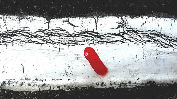Image of a red tab on weathered white paint on a black worn wall